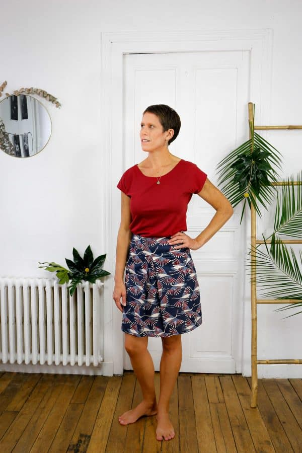 jupe courte imprimé oiseaux portée jambe nue et tee-shirt rouge